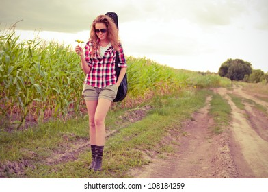 Young redhead woman with guitar passes corn field outdoors in summer by dirt road. Split toning.