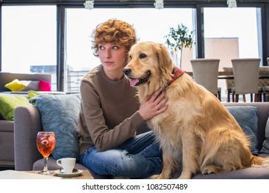 Young redhead woman with her dog in cafe. Looking of the side