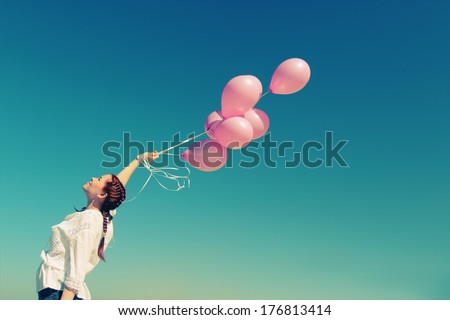 Young redhead woman holding pink balloons