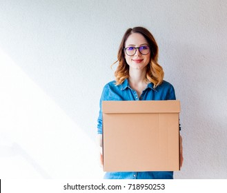 young redhead woman in jeans shirt standing on white wall with moving box. European ethnicity