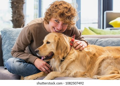 Young redhead woman looking at camera while cuddling her dog