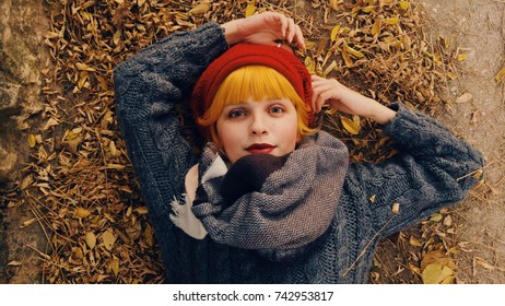 Young redhead woman lying down over a lot of dry autumn leaves