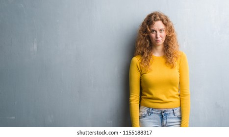 Young redhead woman over grey grunge wall skeptic and nervous, frowning upset because of problem. Negative person.