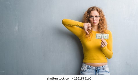 Young redhead woman over grey grunge wall holding a dollar with angry face, negative sign showing dislike with thumbs down, rejection concept