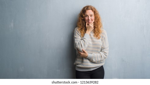 Young redhead woman over grey grunge wall looking confident at the camera with smile with crossed arms and hand raised on chin. Thinking positive.