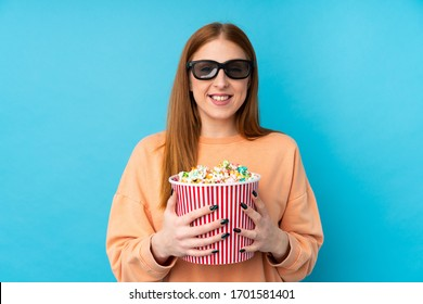 Young redhead woman over isolated background with 3d glasses and holding a big bucket of popcorns