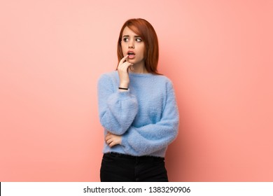 Young redhead woman over pink background having doubts while looking up