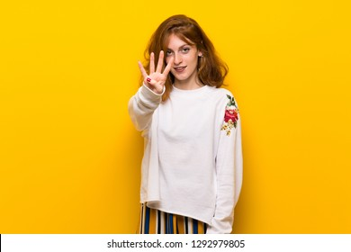 Young redhead woman over yellow wall happy and counting four with fingers