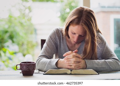 A young redhead woman praying at home during morning devotional.