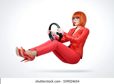 Young redhead woman in red suit driver car with steering wheel, auto concept