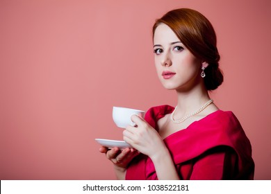 Young redhead woman in red Victorian epoch clothes with cup of tea on pink background