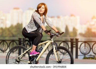 Young redhead woman riding a bike on embankment. Active people outdoors. Sport lifestyle