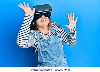 Young redhead woman scared using 3d virtual glasses standing over isolated blue background.