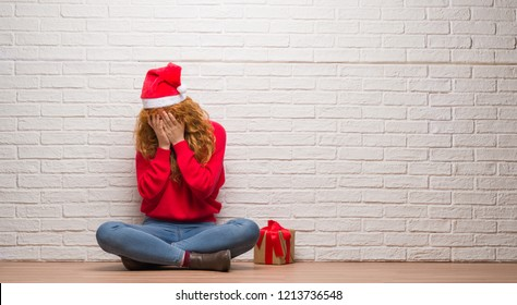 Young redhead woman sitting over brick wall wearing christmas hat with sad expression covering face with hands while crying. Depression concept.
