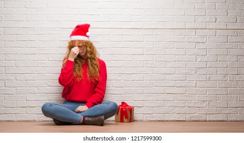 Young redhead woman sitting over brick wall wearing christmas hat tired rubbing nose and eyes feeling fatigue and headache. Stress and frustration concept.
