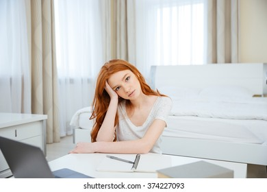 Young redhead woman sitting at the table with her homework at home and looking at camera