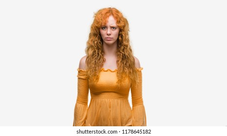 Young redhead woman skeptic and nervous, frowning upset because of problem. Negative person.