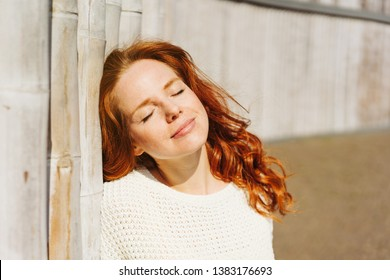 Young redhead woman soaking up the sun on her face with a blissful smile and closed eyes as she leans against an old wall