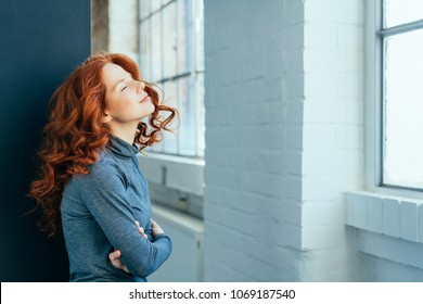 Young redhead woman standing daydreaming with folded arms, closed eyes and a serene expression in front of a window indoors
