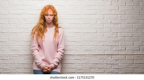 Young redhead woman standing over brick wall skeptic and nervous, frowning upset because of problem. Negative person.