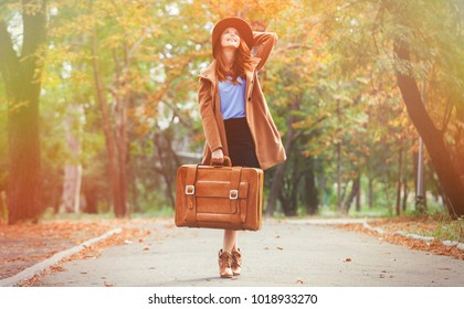 Young redhead woman with suitcase at autumn season park.