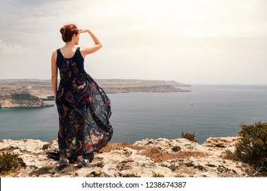 Young redhead woman with a topknot looking far away the sea with her hand over head since a cliff with her long dress moving with wind