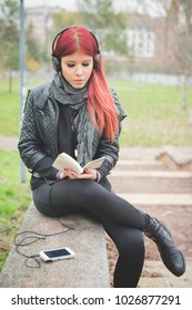 young redhead woman venezuelan listening music with headphones reading book - freedom, enjoying, relaxing concept