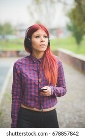 young redhead woman venezuelan listening music looking away with headphones and smart phone hand hold - freedom, enjoying, relaxing concept
