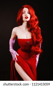 Young redhead woman with very long hair in red gown on a black background. A beautiful girl with pale skin, red lips and blue eyes. Sexy gown on a beautiful slim figure. Long pink gloves