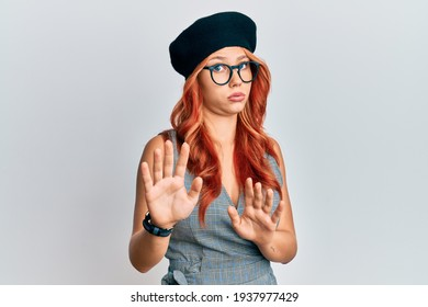 Young redhead woman wearing fashion french look with beret moving away hands palms showing refusal and denial with afraid and disgusting expression. stop and forbidden.