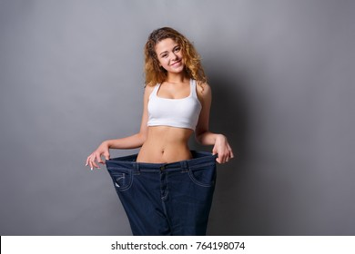 Young redhead woman wearing jeans much bigger size after loosing weight from diet, gray studio background, copy space. Healthy eating, bodybuilding concept