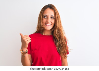 Young redhead woman wearing red casual t-shirt stading over white isolated background smiling with happy face looking and pointing to the side with thumb up.