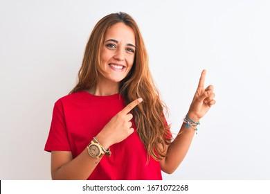 Joven mujer pelirroja con un pantalones T casual rojo sobre fondo blanco aislado sonriendo y mirando a la cámara apuntando con dos manos y dedos al lado.