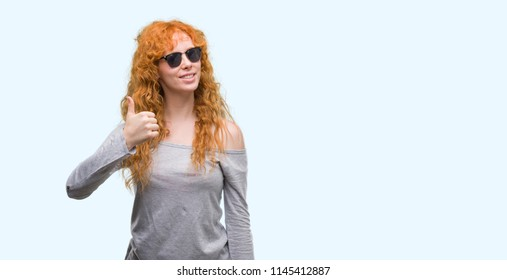 Young redhead woman wearing sunglasses happy with big smile doing ok sign, thumb up with fingers, excellent sign