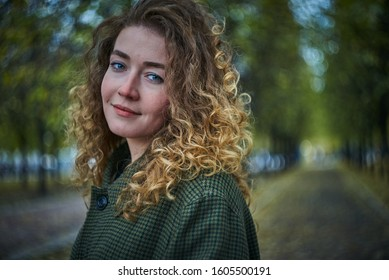 Young redheaded caucasian woman in a green jacket outdoors in an autumn park