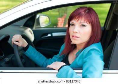 Young redheaded woman sitting behind the wheel of the car