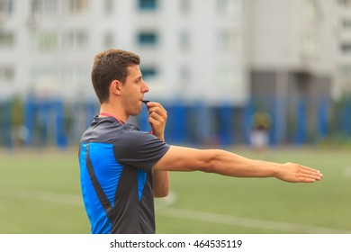 young referee whistles and indicates a hand on the football field