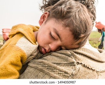 a young refugee child is sleeping on the shoulder of his father and both looks so tired hungry and terrified