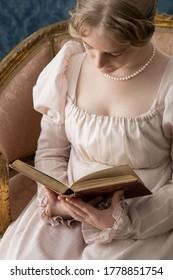 A young Regency woman in a pink dress in a Regency room
