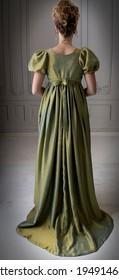 A young Regency woman wearing a silk dress shown in back view