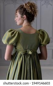 A young Regency woman wearing a silk dress shown in back view - Shutterstock ID 1949146603