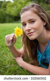 Young relaxed girl lying on the grass in the countryside while holding a yellow flower