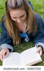 Young relaxed girl lying on the grass in the countryside while reading a book
