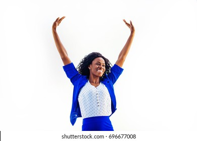 a young relaxed and happy african woman wearing formals standing with her hands up
