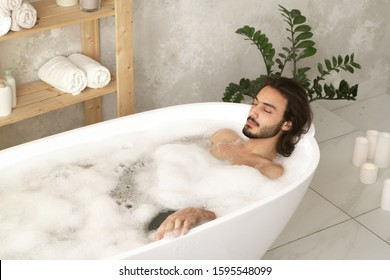 Young relaxed man with closed eyes lying in white bathtub filled with hot water and foam with wooden shelves near by