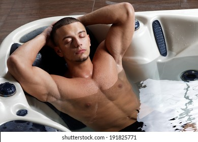 Young relaxed man in jacuzzi. Spa.