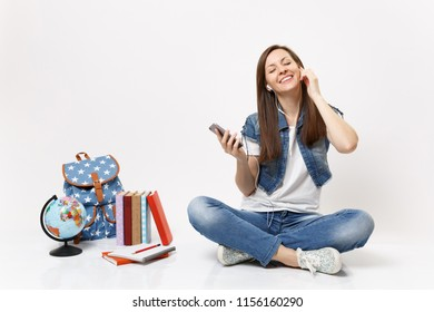 Young relaxed smiling woman student with earphones listening music holding mobile phone sit near globe backpack school books isolated on white background. Education in high school university college