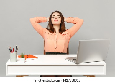 Young relaxed woman keeping eyes closed, sleep with hands behind head, sit work at desk with pc laptop isolated on gray background. Achievement business career lifestyle concept. Mock up copy space
