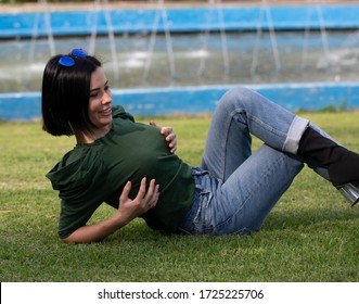 Young relaxed woman on blurred nature background. Beautiful girl walking at the park near fountain