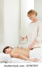 Young relaxed woman receiving fire cupping from a professional acupuncture therapist